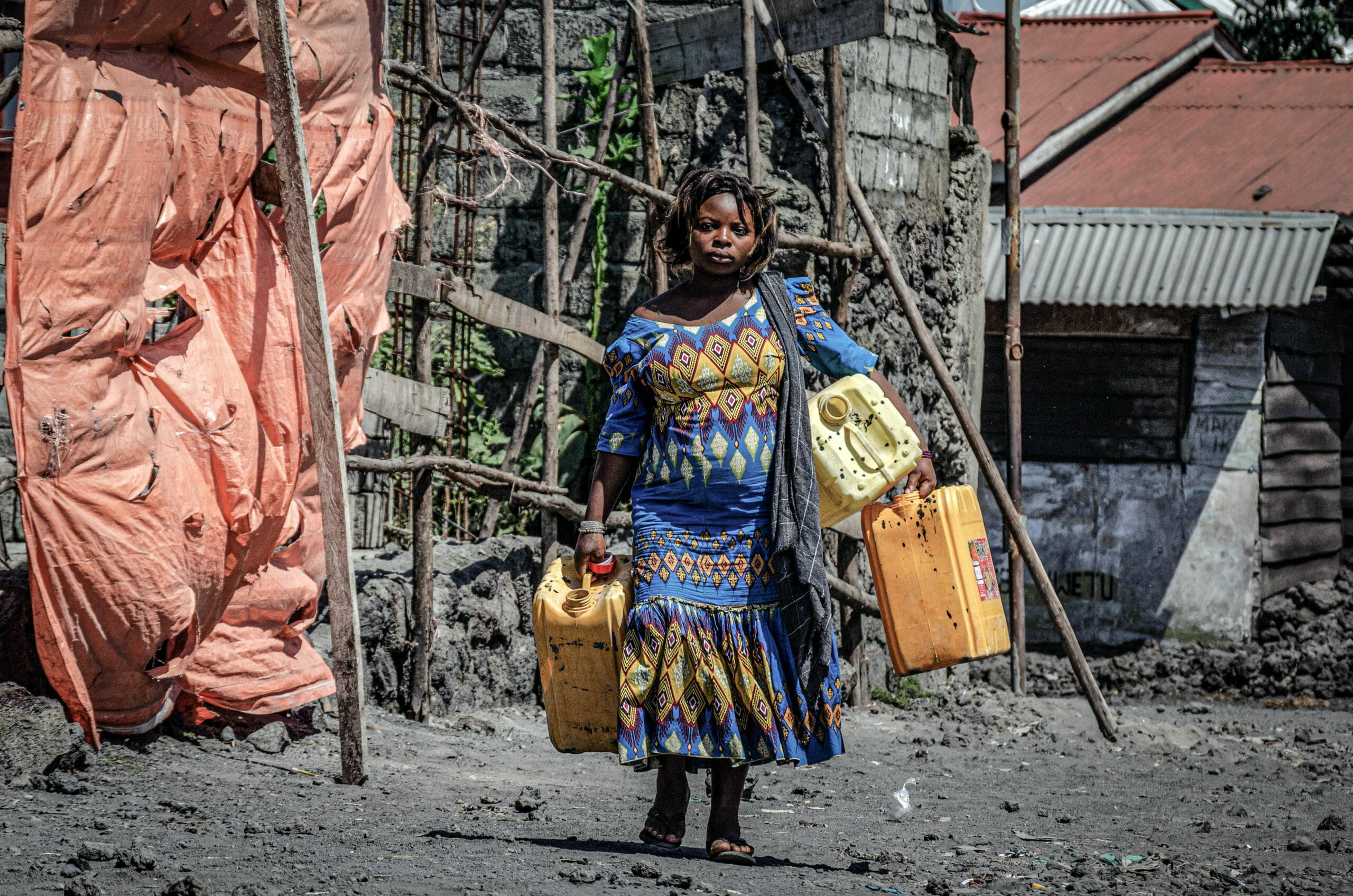 Goma, Democratic Republic of Congo, May 2020. A woman carries water containers in Goma, the capital of eastern Congo's North Kivu Province last month. Congo's state water provider Regideso promised free access to water at the start of the coronavirus outbreak in March, but with few people connected to water mains and poor service for those who are, the lack of water during the pandemic has made it difficult to adhere to health advisories and hygiene measures and has led to protests in Goma, which sits on the shores of Lake Kivu. © Arlette Bashizi for Fondation Carmignac