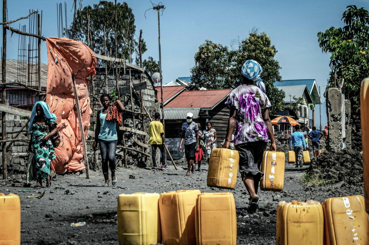 Goma, Democratic Republic of Congo, May 2020. A woman carries water containers in Goma, the capital of eastern Congo's North Kivu Province last month. Goma's residents can spend hours waiting in line for access to communal pumps and often spend the early morning hours waiting their turn. © Arlette Bashizi for Fondation Carmignac