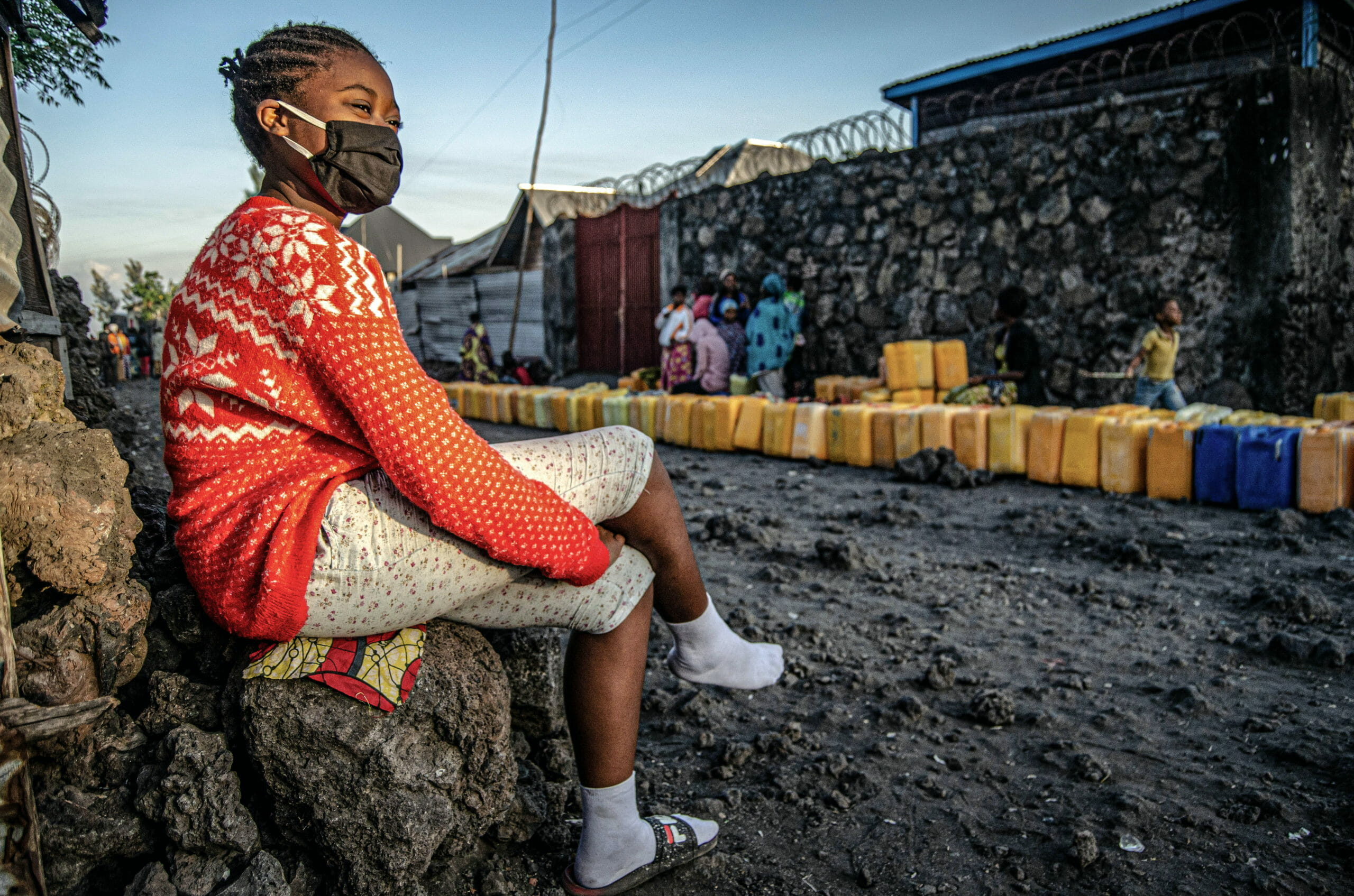Goma, Democratic Republic of Congo, May 2020. A girl waits to fill water containers in Goma, the capital of eastern Congo's North Kivu Province last month. Water collection in Congo is usually done by women and girls who are put at risk of sexual violence in remote areas or during hours of darkness. Without private latrines, women and girls must also find isolated locations to go to the toilet, often at night, again putting them at risk of being raped. © Arlette Bashizi for Fondation Carmignac