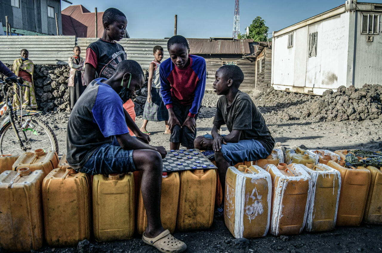 Goma, Democratic Republic of Congo, May 2020. Boys play a board game while waiting to fill water containers in Goma last month. © Arlette Bashizi for Fondation Carmignac
