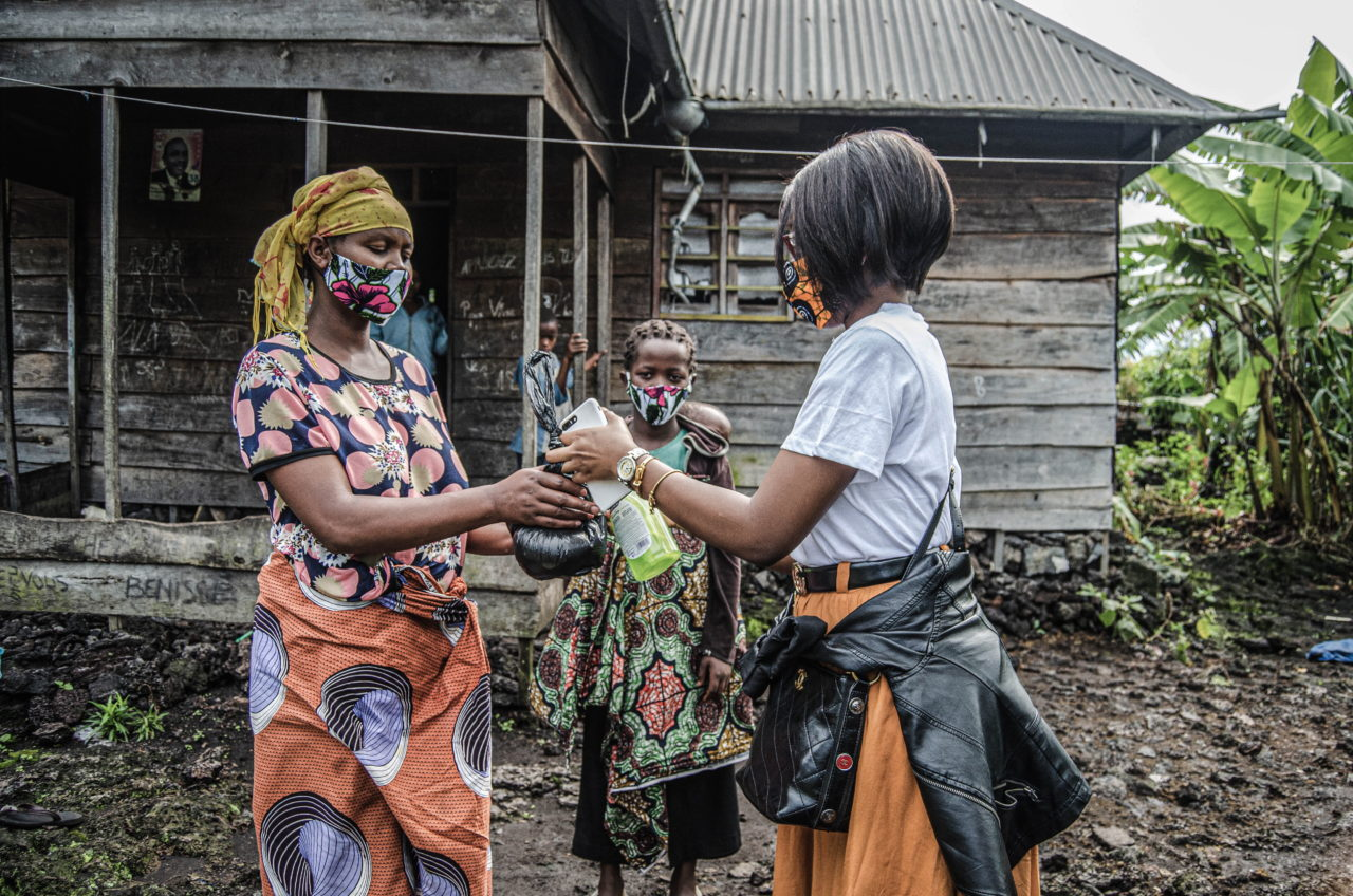 Goma, DRC, May 2020. A woman living in the Munigi neighborhood of the eastern Congolese city of Goma receives a mask and sanitary supplies provided by the Bahati Foundation in May. © Arlette Bashizi for Fondation Carmignac