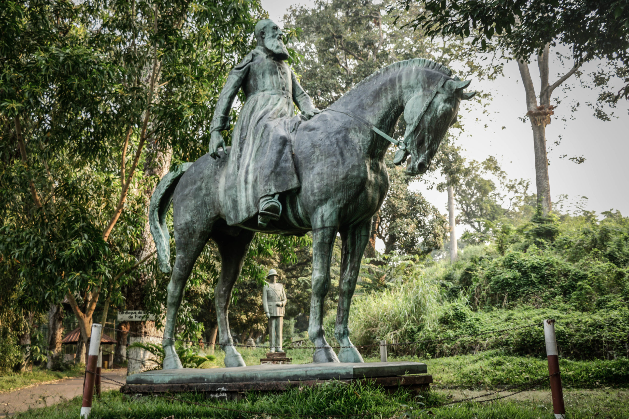 """Kinshasa, Democratic Republic of Congo, June 2020. A six-meter statue of King Leopold II at the Institute of National Museums of Congo, in the Mont Ngaliema area of the capital Kinshasa last week. Inaugurated in 1928 by Albert I, the work was first installed in front of the Palace of the Nation, where the presidency is currently located. The monument was removed in 1967 on the orders of then dictator Mobutu Sese Seko, at the height of his """"return to national and African authenticity"""" policy that sought to rename colonial places. Forgotten for almost four decades, the statue made a sudden reappearance in Kinshasa city centre, on the June 30 Boulevard - the date of independence - in February 2005. For unknown reasons, the statue was taken down again after 24 hours, by the same workers who had erected it. The statue finally reached Ngaliema Park, rehabilitated in 2010 with the help of the United Nations Mission in the Congo, known as Monusco. A statue of King Albert I, Leopold's nephew and successor, can be seen beneath the horse. © Justin Makangara for Fondation Carmignac"""