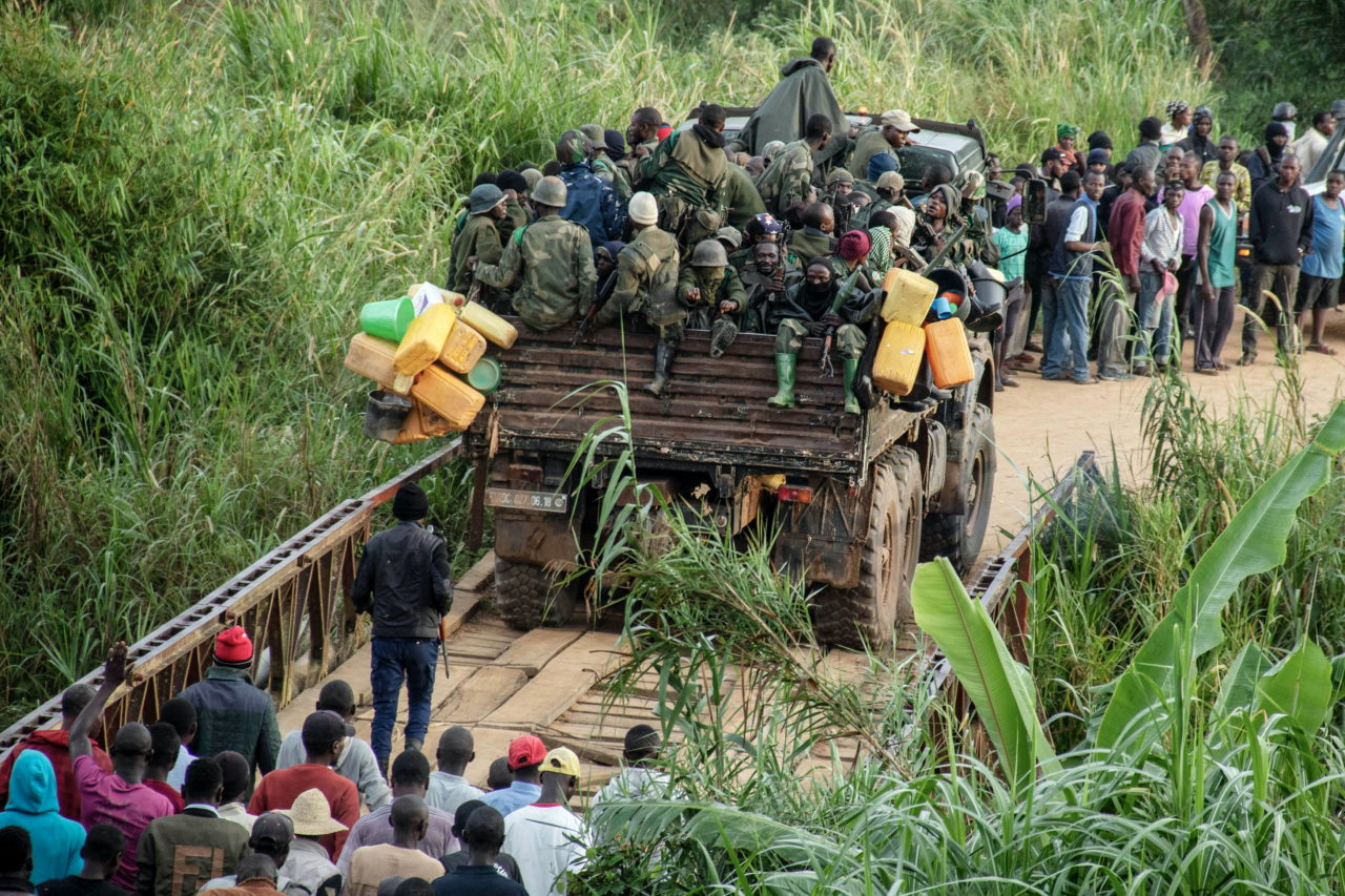 """Northeastern Ituri Province, DRC, April 2020. Congolese government troops ride a truck past people fleeing their villages as they deploy toward the front line about 15 kilometers north of the city of Bunia in Congo's northeastern Ituri Province during clashes against the Cooperative for the Development of Congo (CODECO), an armed political-religious sect drawn from the Lendu ethnic group, in mid-April. Assailants from the CODECO militia had just killed 22 people in the village of Koli while they were asleep, according to local officials in the town of Djugu, who said all the dead were from the Hema ethnic group. Conflict between the Lendu, mainly farmers, and the Hema, herders and traders, has a long history in the gold and oil-rich province, with tens of thousands of people killed between 1999 and 2003. Militia attacks have killed at least 444 civilians in Ituri since March and displaced more than 200,000 people since the beginning of the year, according Human Rights Watch (HRW), which cited United Nations sources. A January UN report that said some of deaths could constitute a """"crime against humanity"""". The army launched an offensive in January against militias operating in Ituri as part of a wider offensive launched last October, and announced that CODECO's leader, Justin Ngudjolo, was killed in late March.The group has since split into different factions and continues to kill civilians across the province, according to HRW, which said Congolese security forces fighting the militia have also committed serious abuses, including extrajudicial executions. © Dieudonne Dirole for Fondation Carmignac"""