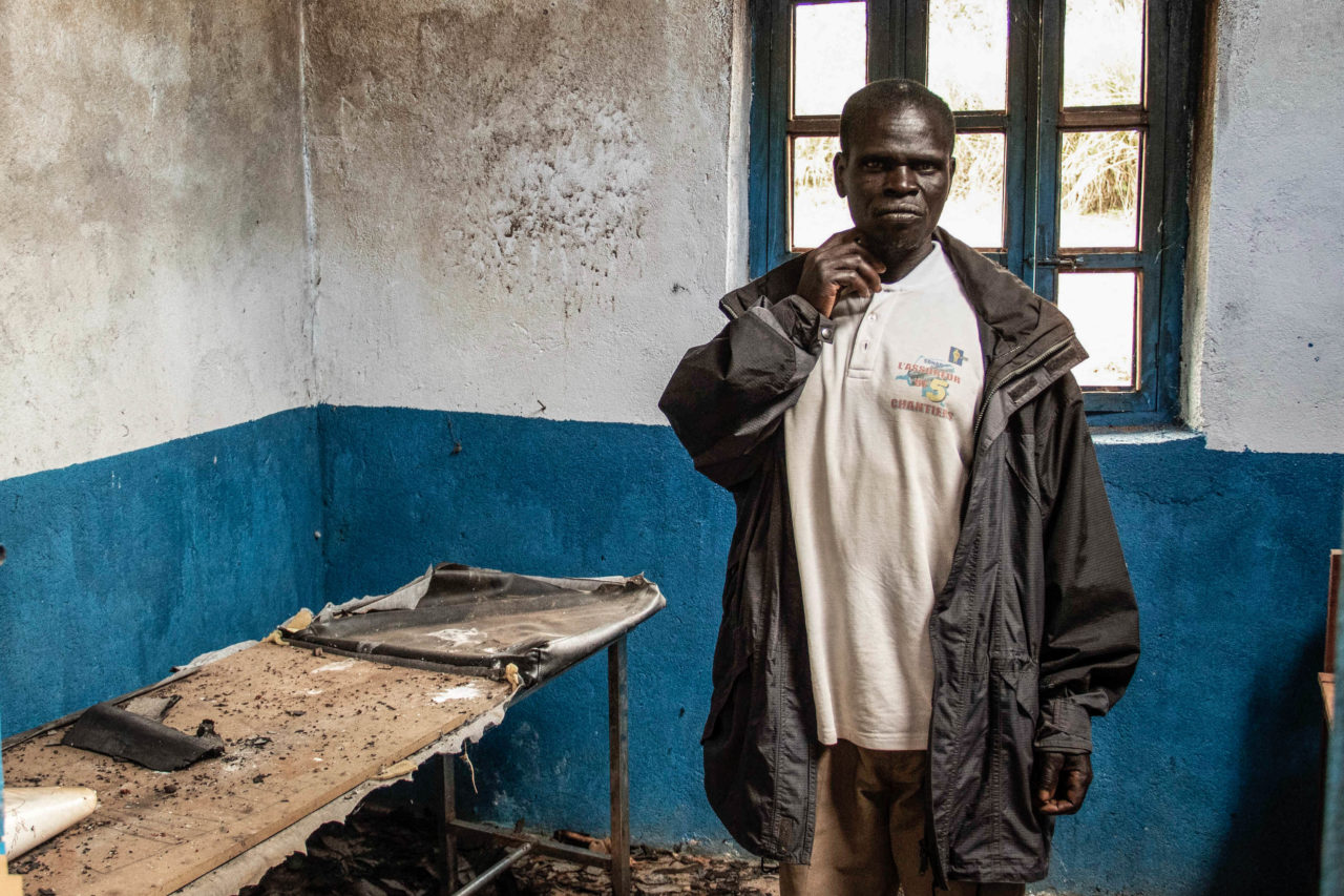 Tche, DRC, February 2020. A village chief stands in the destroyed health clinic in the village of Tche in Ituri province in February. A series of massacres in villages in Djugu territory, including Tche, killed 161 people in early June 2019 and killings in the area have continued in 2020. Hospitals and health clinics have been destroyed and burned during the ongoing conflict between the Hema and Lendu ethnic groups in the area. © Dieudonne Dirole for Fondation Carmignac