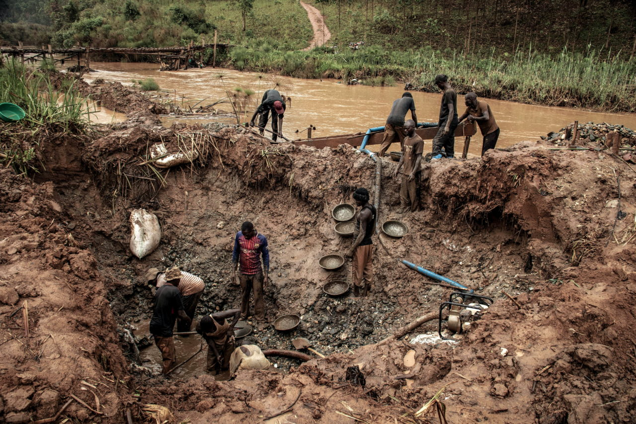"""Bambissa, DRC, February 2020. Artisanal miners extract gold from the alluvial sediments of the Nizi River near the village of Bambissa in Congo's northeastern Ituri Province in February. Much of the bloodshed in Ituri has its roots in competition over gold mines, according to Human Rights Watch. Local mines have long been a source of cash for ex-rebels, politicians, and Congolese military officials who are involved in smuggling gold into neighboring Uganda and South Sudan. Gold is mined by artisanal mining cooperatives, typically using rudimentary tools and techniques. Most cooperatives and mining companies in the province do not report production figures, and minerals are illegally marketed, causing """"massive fraud"""" of huge quantities, according to Reuters. Measures to curb the coronavirus worldwide have disrupted the supply chains artisanal gold miners depend on and dried up funding, causing local gold prices to slump to discounts of as much as 40% to the world price, the news agency reported. In one area of Ituri, 79 out of 85 gold trading houses have shut down because they have no one to sell to, research by Canadian natural resources NGO IMPACT found. © Dieudonne Dirole for Fondation Carmignac"""