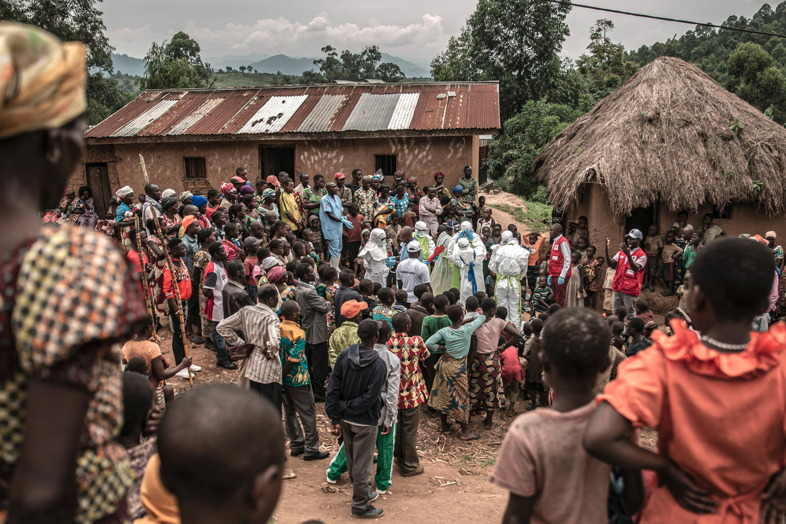 Rutshuru, North Kivu Province, February 2020. Neighbors and Red Cross burial workers dressed in protective clothing gather outside a family home in Rutshuru, where an 11-month-old girl died during the Ebola outbreak. © Finbarr O'Reilly for Fondation Carmignac