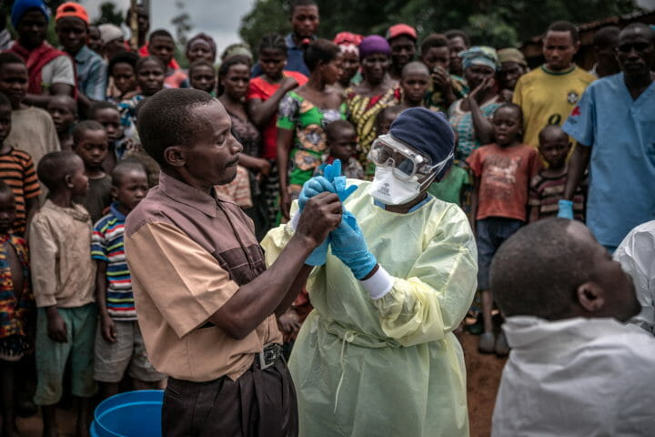 A Red Cross burial worker shows a man how to put on protective gloves before the inspection of the body of an 11-month old girl who died during the Ebola outbreak in the town of Rutshuru in North Kivu province, February 2020. © Finbarr O'Reilly / Fondation Carmignac