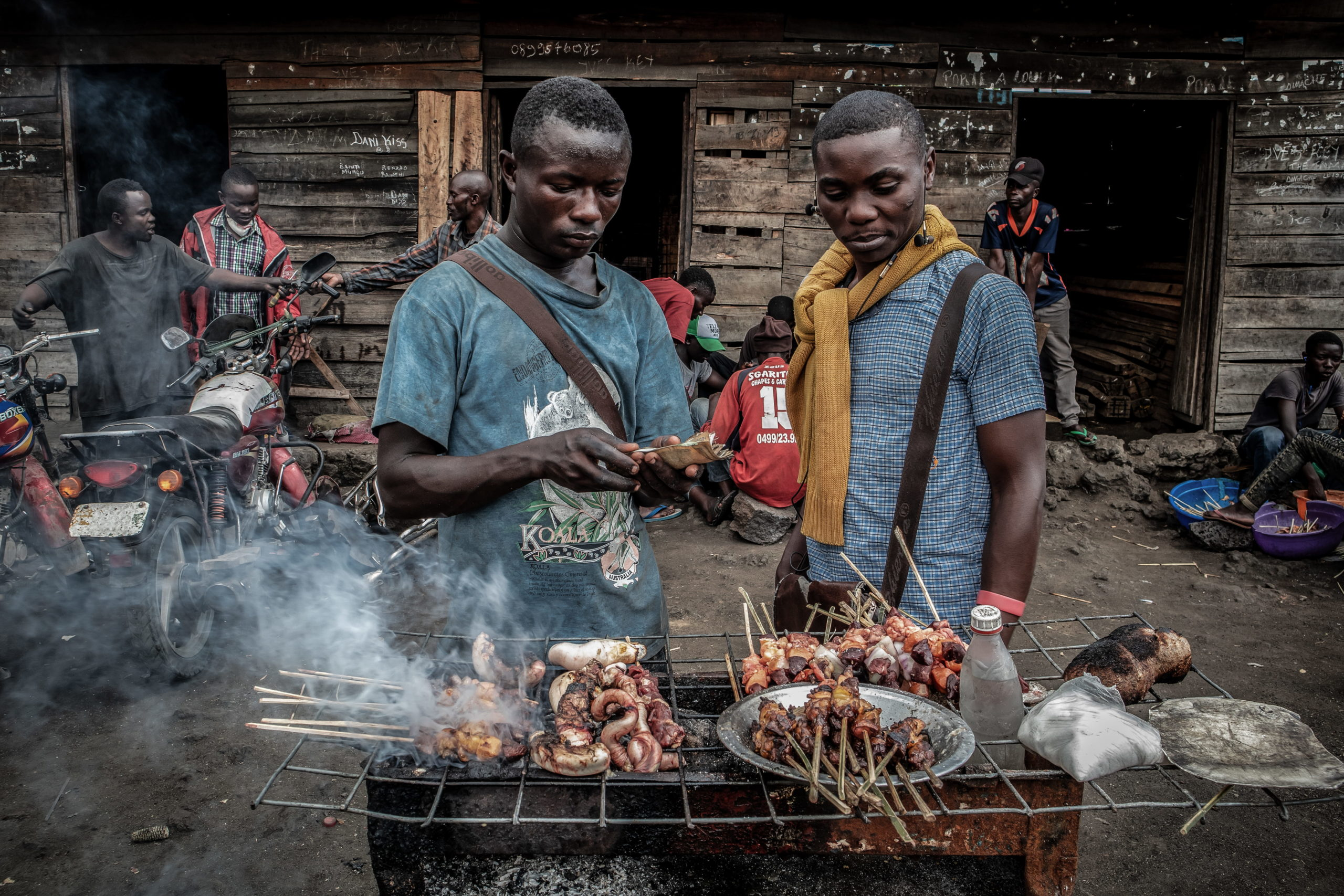 Goma surroundings, DRC, December 2020. Balume Benjamin, 19, (L), sells brochettes cooked on a charcoal grill on the roadside outside the eastern Congolese city of Goma. © Guerchom Ndebo for Fondation Carmignac
