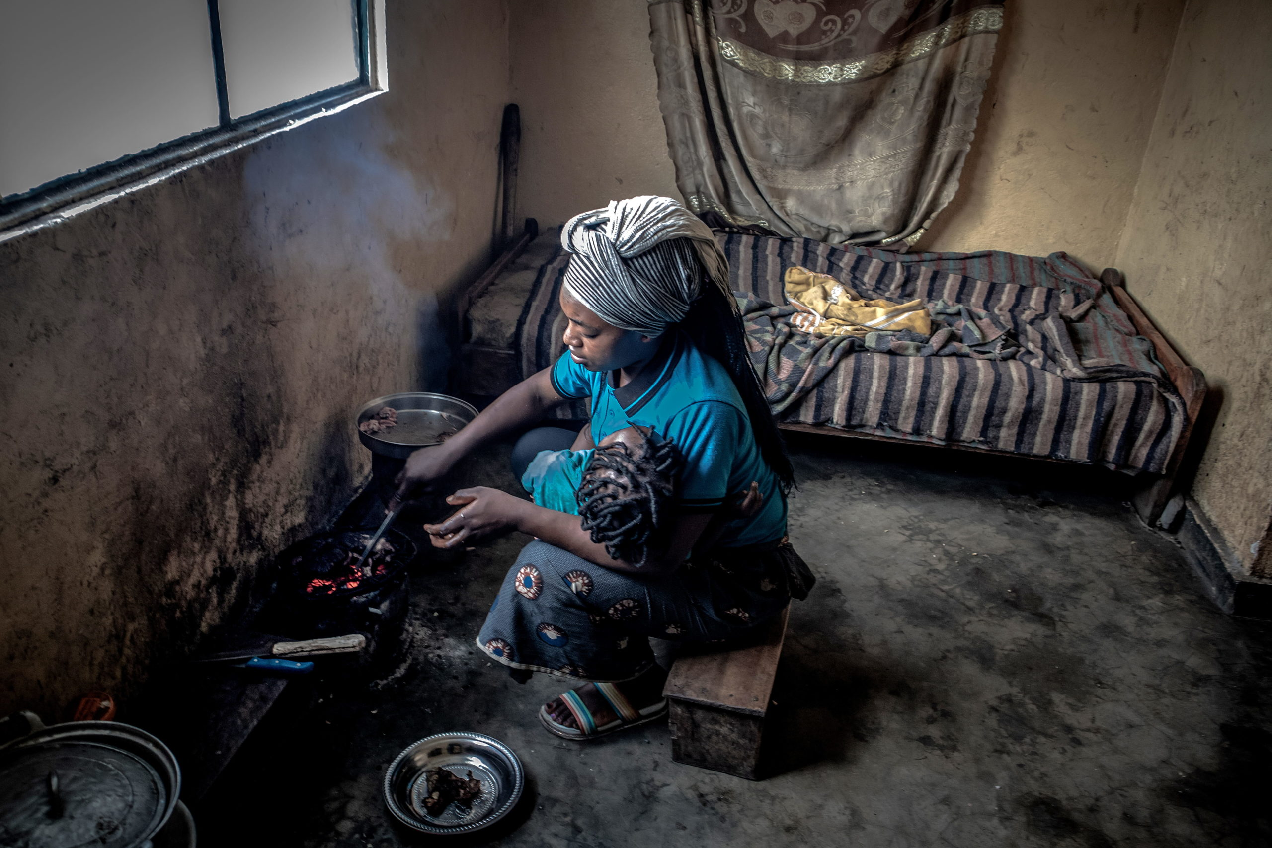 Minova, DRC, December 2020. Charmante prepares a meal on a charcoal stove inside her home in the eastern Congolese town of Minova. © Guerchom Ndebo for Fondation Carmignac