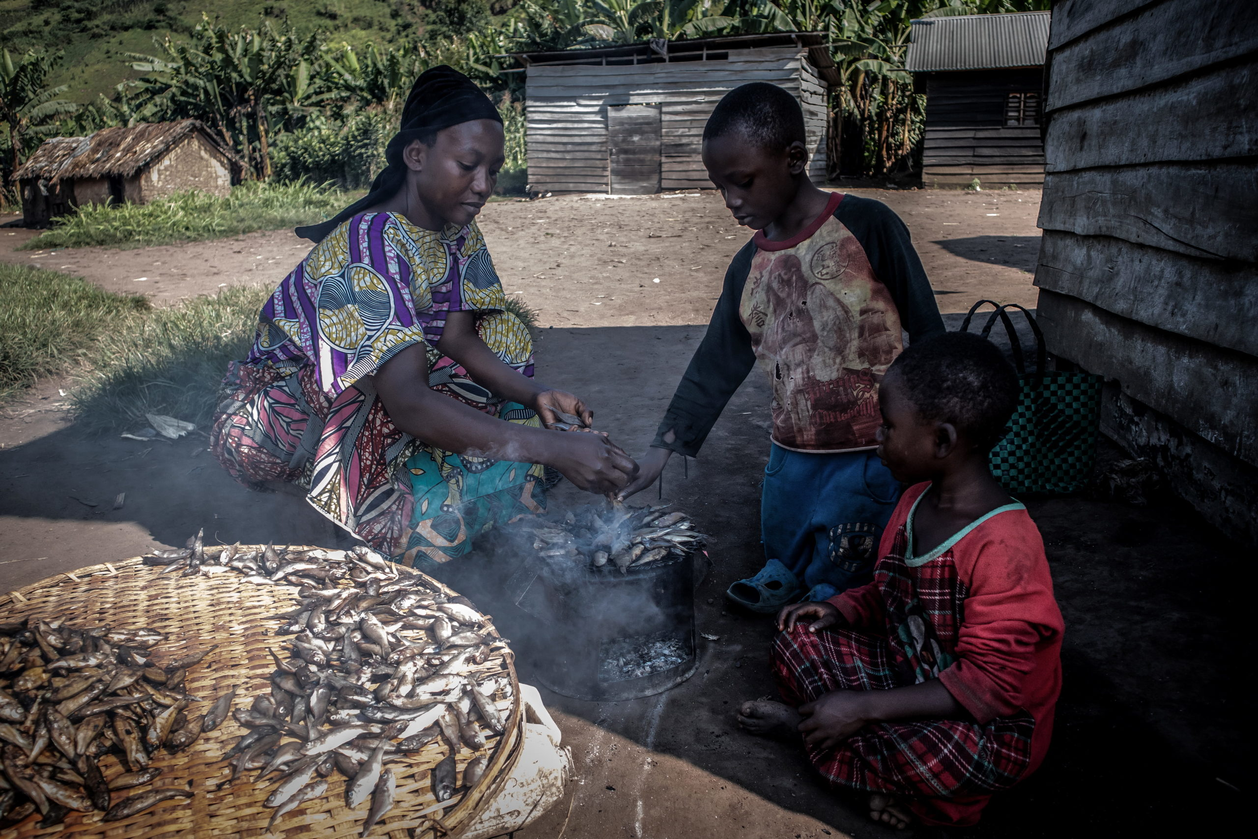 Minova, DRC, December 2020. A woman prepares a meal of Sambaza, or fried fish, on a charcoal stove inside her home in the eastern Congolese town of Minova. © Guerchom Ndebo for Fondation Carmignac