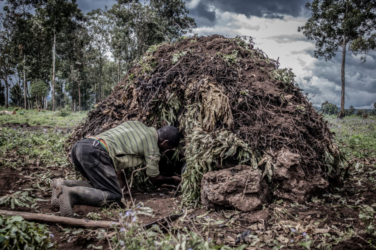 Virunga National Park, DRC, November 2020. A man fuels a kiln to make charcoal on a swathe of deforested land on the edge of Virunga National Park just north of the eastern Congolese city of Goma. © Guerchom Ndebo for Fondation Carmignac