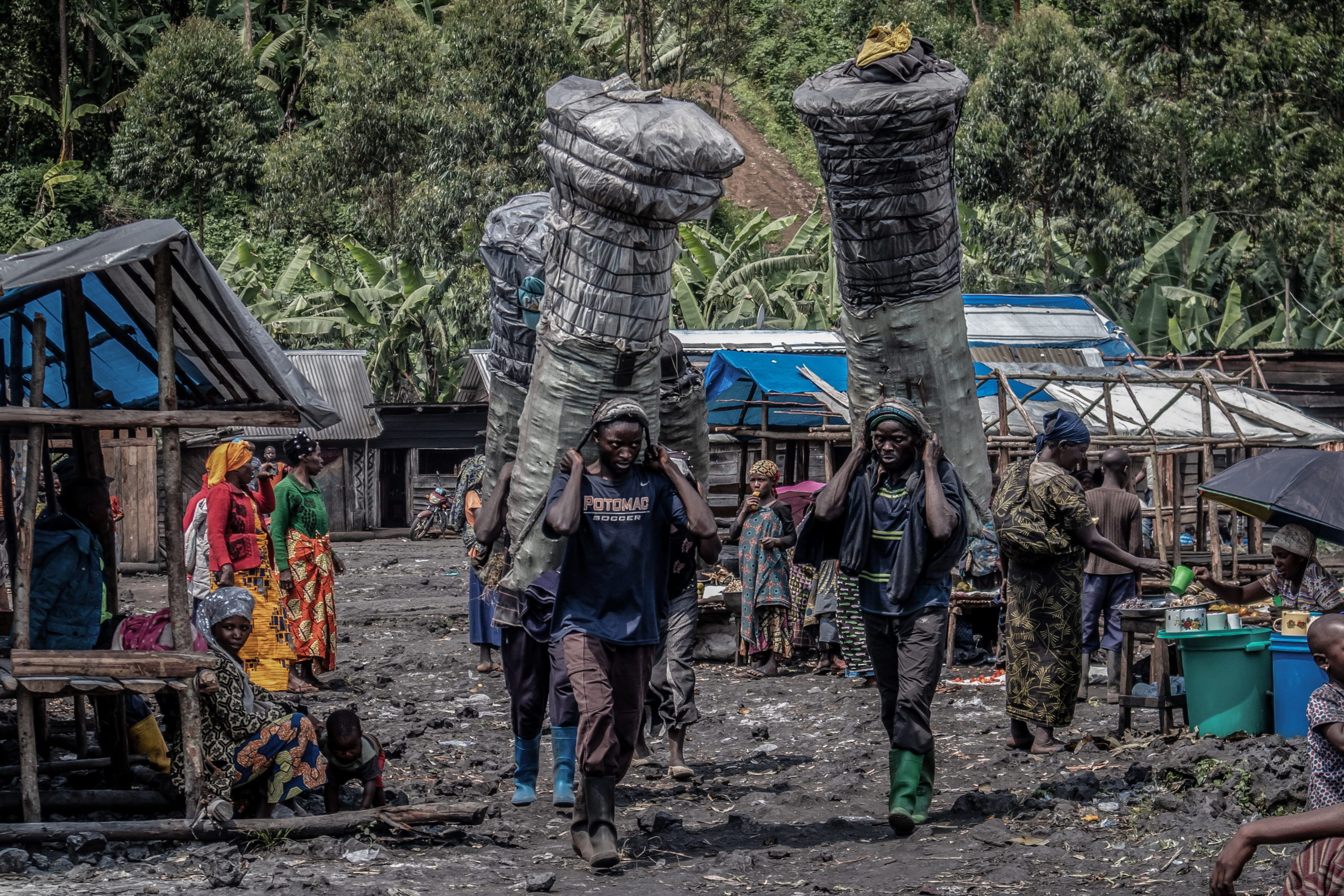 Virunga National Park, DRC, December 2020. Men transport charcoal at the roadside market of Kulupango on the edge of Virunga National Park just north of the eastern Congolese city of Goma. Most of the charcoal bound for Goma passes through Kulupango market. © Guerchom Ndebo for Fondation Carmignac