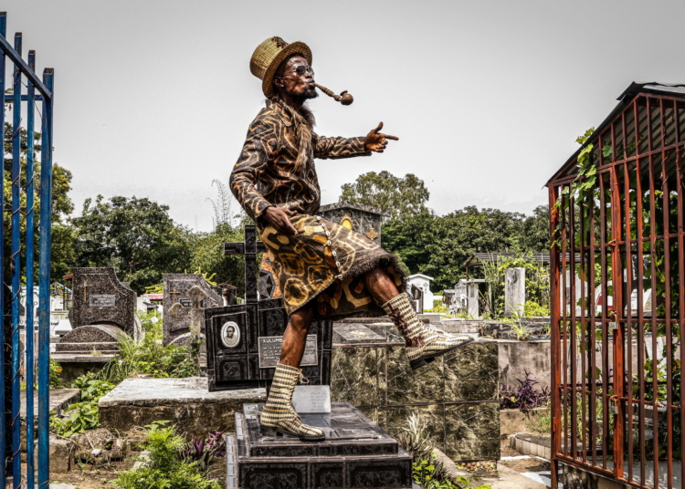 Kinshasa, DRC, February 2021. Sapeur Koko Lingwala poses atop a grave in the cemetery in the Gombe neighbourhood of Kinshasa on February 10 to commemorate the anniversary of the death of Stervos Niarcos, who died 26 years ago in Paris and is revered as the founder of modern sapeurism, the Society of Tastemakers and Elegant People (or Société des Ambianceurs et des Personnes Élégantes in the original French, or SAPE for short). © Justin Makangara for Fondation Carmignac