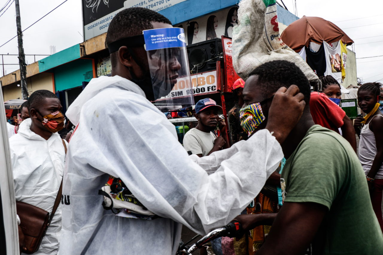 Kinshasa, DRC, May 2020. A member of the pro-democracy and civil society movement Filimibi (« whistle » in swahili) hands out masks while carrying out a public educational campaign about coronavirus in a market in Congo's capital Kinshasa in May. © Justin Makangara for Fondation Carmignac