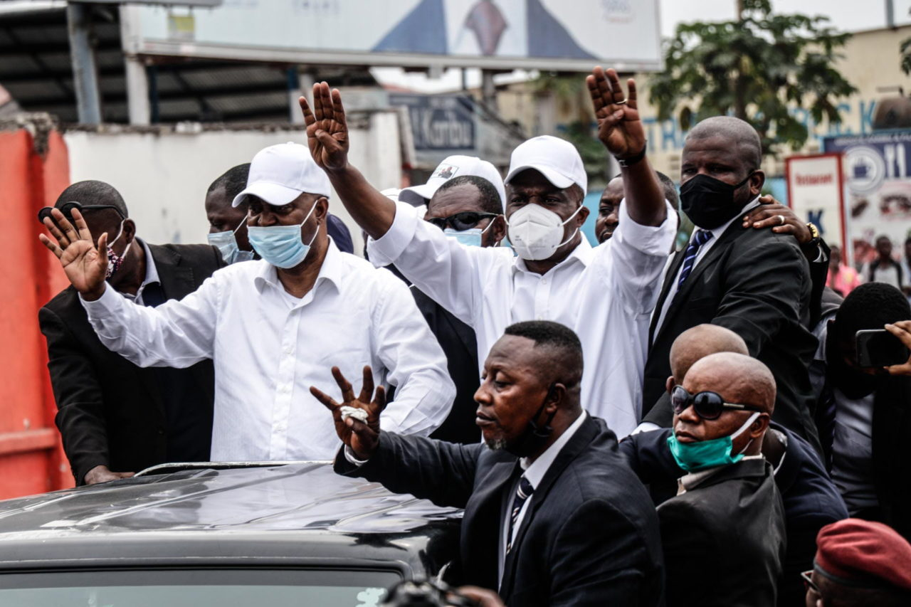 Kinshasa, DRC, August 23th 2020. Lamuka opposition party leader Martin Fayulu (right, in white) makes the gesture for the number four, his candidate number in the 2018 presidential election, as he returned to Kinshasa this week after being stuck in the United States for five months due to coronavirus travel restrictions. © Justin Makangara for Fondation Carmignac