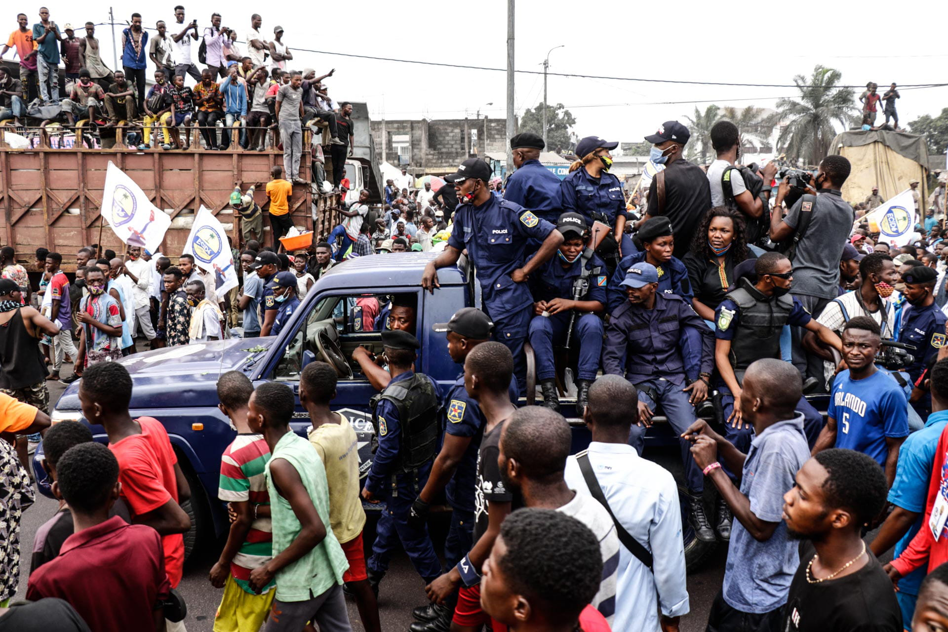 Kinshasa, DRC, August 23th 2020. Police watch as supporters line the streets waiting to catch a glimpse of Lamuka opposition party leader Martin Fayulu as he returned to Kinshasa this week after being stuck in the United States for five months due to coronavirus travel restrictions. © Justin Makangara for Fondation Carmignac