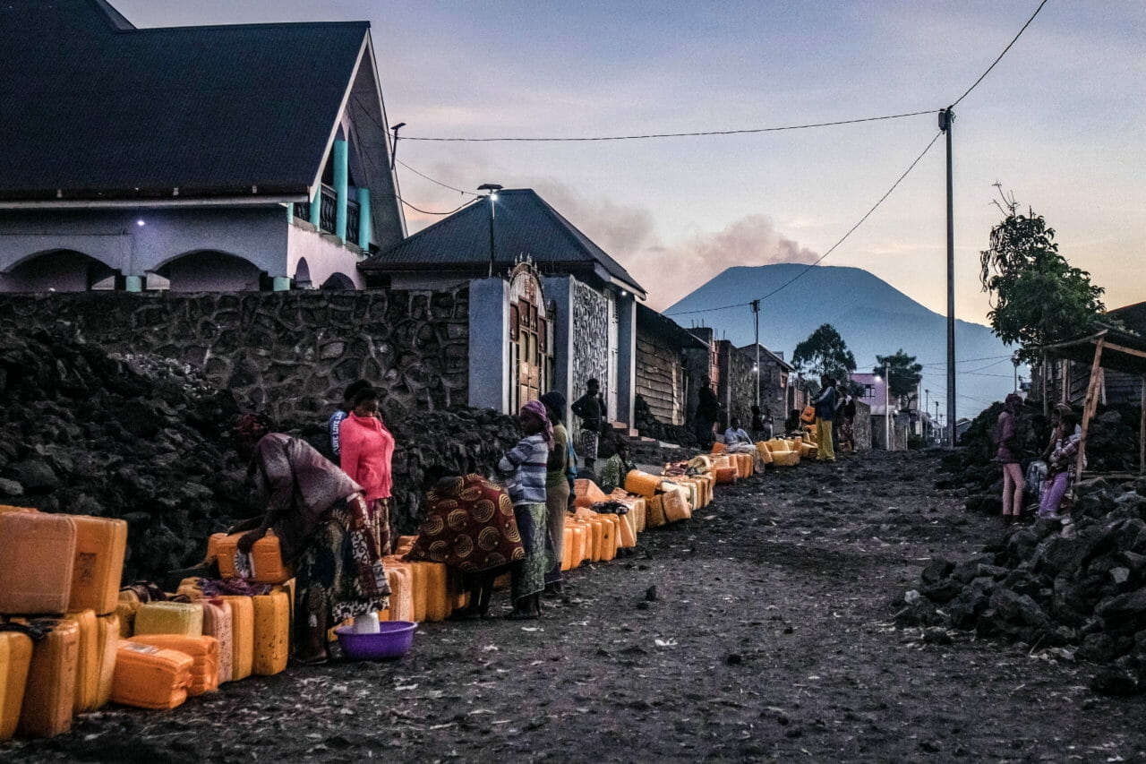 Goma, Democratic Republic of Congo, June 2020. A man rests on water containers while waiting his turn to fill them at a communal tap in Goma, the capital of eastern Congo's North Kivu Province this month. Goma's residents can spend hours waiting in line for access to communal pumps and often spend the early morning hours waiting their turn. © Moses Sawasawa for Fondation Carmignac