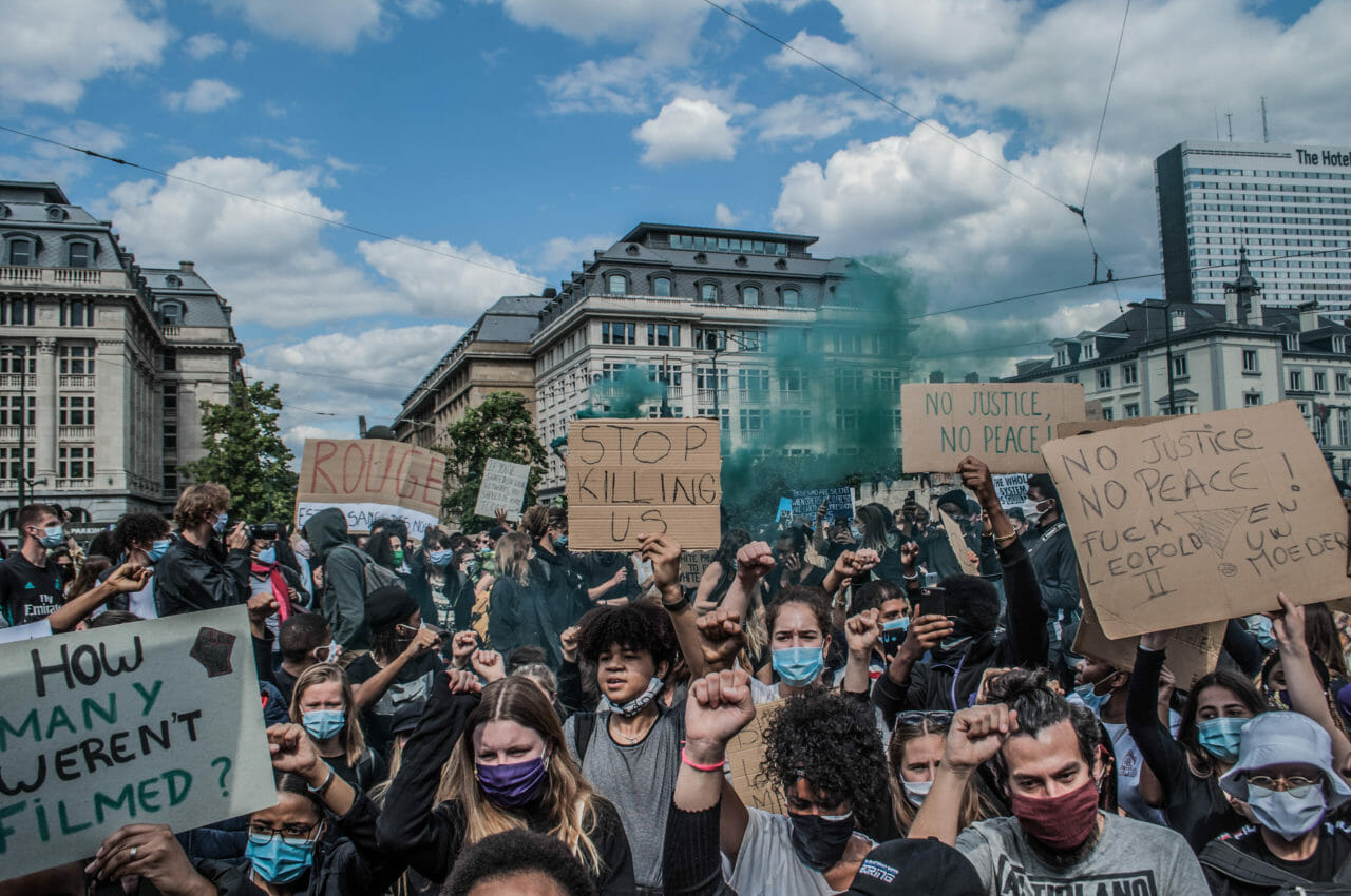 Brussels, Belgium, June 6-7, 2020. Protesters at a Black Lives Matter rally in Brussels this weekend carry a sign (right) denouncing Belgium's imperial exploitation of what is now the Democratic Republic of Congo. As massive gatherings for racial justice gain momentum around the world, activists in Belgium are hoping the global movement may finally shift attitudes toward the colonial legacy of King Leopold II, the monarch whose tyrannical rule over the Congo Free State (now the Democratic Republic of Congo) is blamed for the deaths of between 10-15 million Congolese. © Pamela Tulizo for Fondation Carmignac
