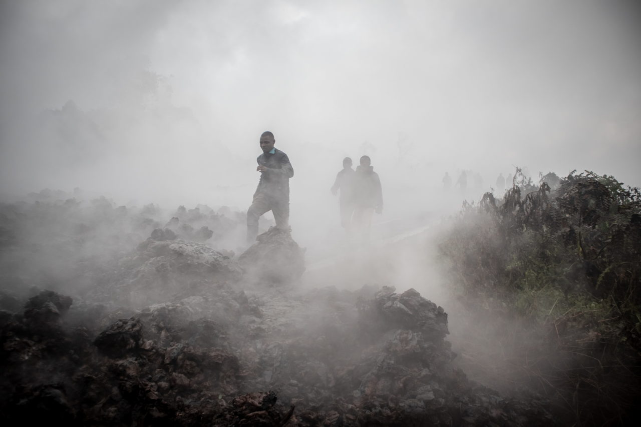 On the morning after the eruption Congo in Conversation photographer Guerchom Ndebo continued to file photographs for Agence France-Press, including this image of people crossing lava still smouldering and releasing noxious gases as it cools.