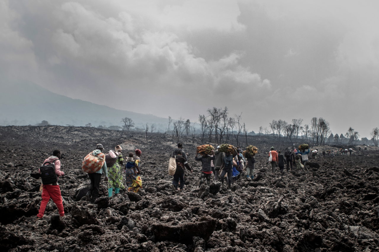 People cross the cooling lava flow in search of a safe place to stay while others transport goods to the market in Goma two days after the eruption. Guerchom Ndebo for Fondation Carmignac