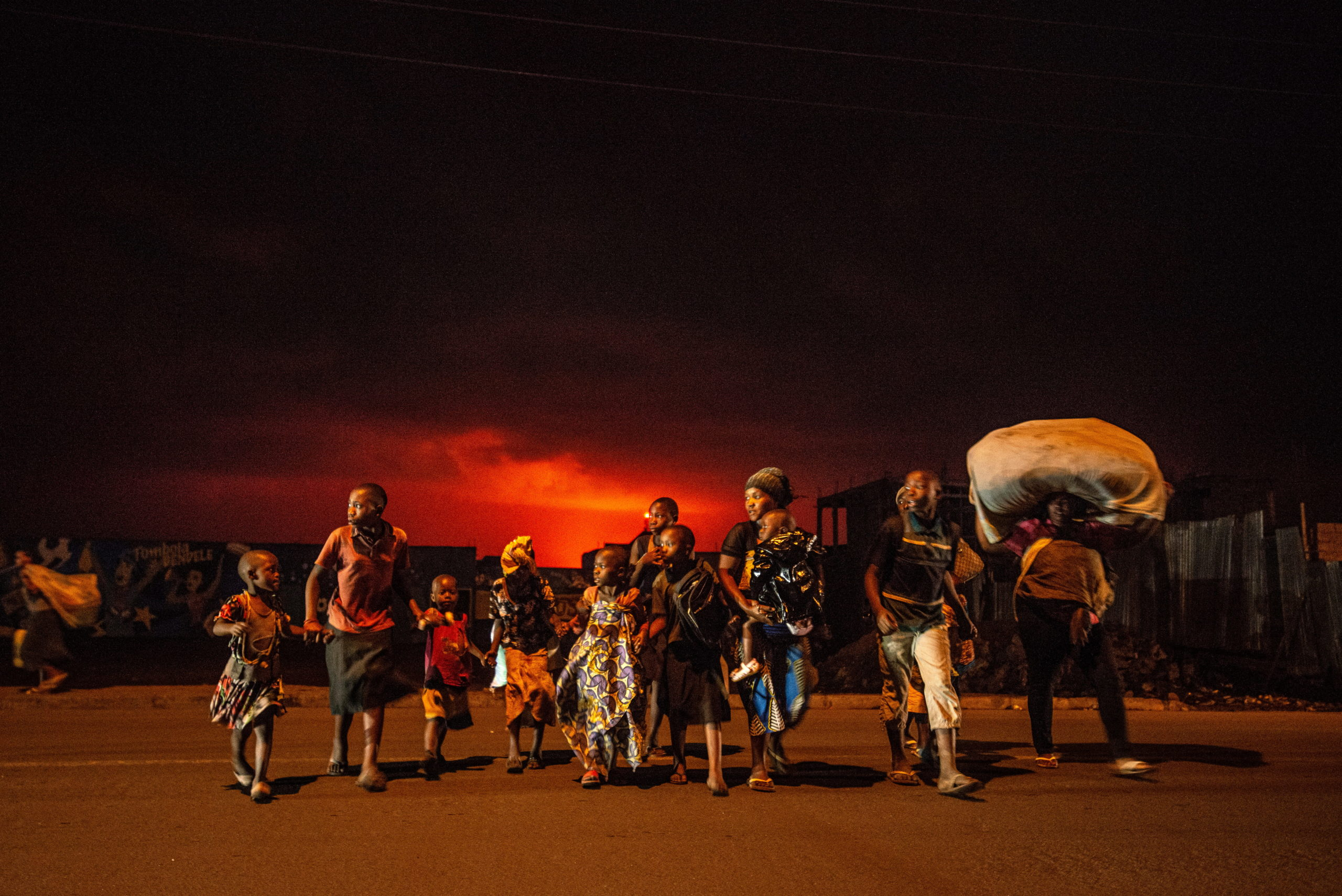 Goma, South Kivu, May 22 2021. At night, residents flee the eruption of Nyiragongo volcano. This image was among the first that Fondation Carmignac's Congo in Conversation contributor Guerchom Ndebo filed to Agence France-Presse within hours of the eruption and it was widely published internationally. Guerchom Ndebo for Fondation Carmignac.