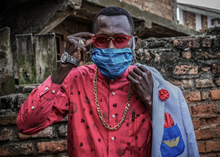 "Bukavu, DRC, May 2020. Anglebert Maurice Kakuja, 29, a Sapeur, or Congolese dandy, shows off his fashion sense while wearing a homemade mask in the eastern Congolese city of Bukavu this week. Sapeurs take their name from the acronym for their group: SAPE, meaning Société des Ambianceurs et des Personnes Élégantes, or ""elegant persons who create ambience"". © Raissa Karama Rwizibuka for Fondation Carmignac"